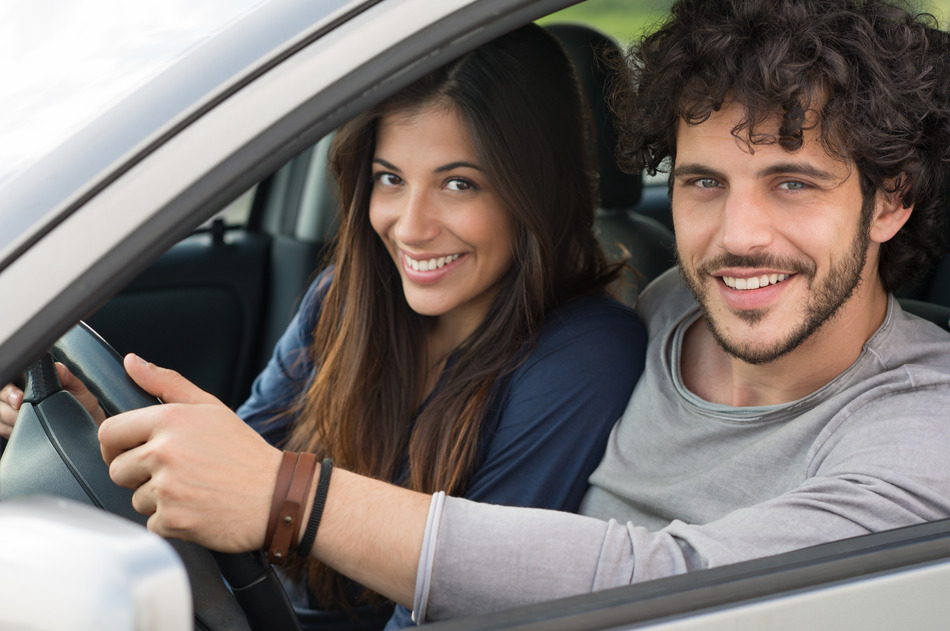Happy Young Couple Sitting In Car