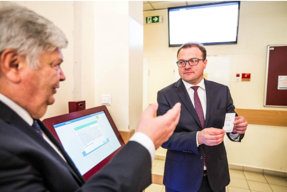 Dyrektor pogotowia (z lewej) prezentuje prezydentowi działanie infokiosku Kowalski prezentuje