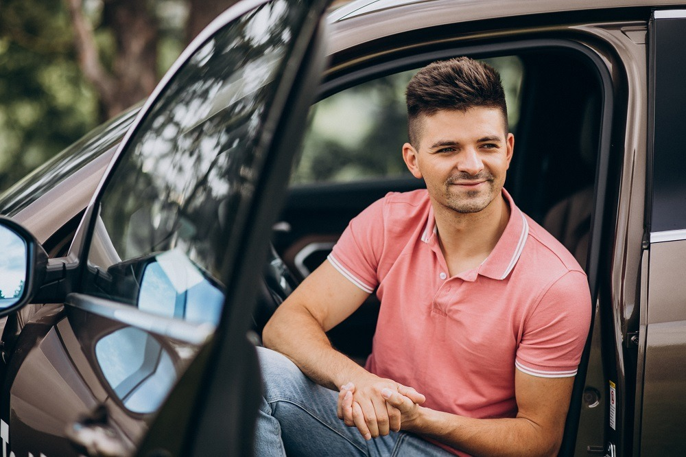 Young handsome man sitting in car
